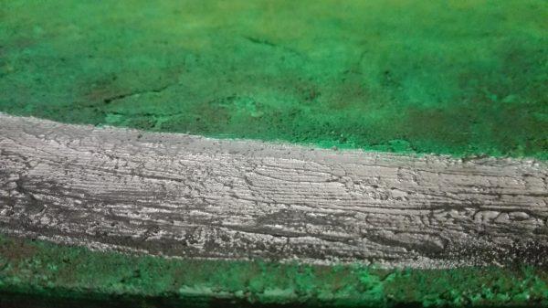Detalles de la cinta del cuadro pintado en verde con acrilico sobre lienzo, representando la familia y amigos de la misma